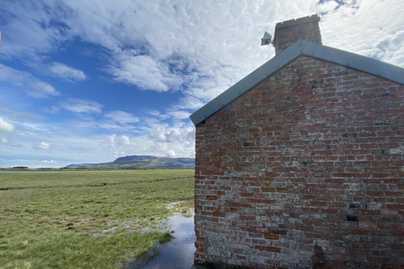 camera-on-top-of-red-brick-building-on-saltmarsh-river-roe